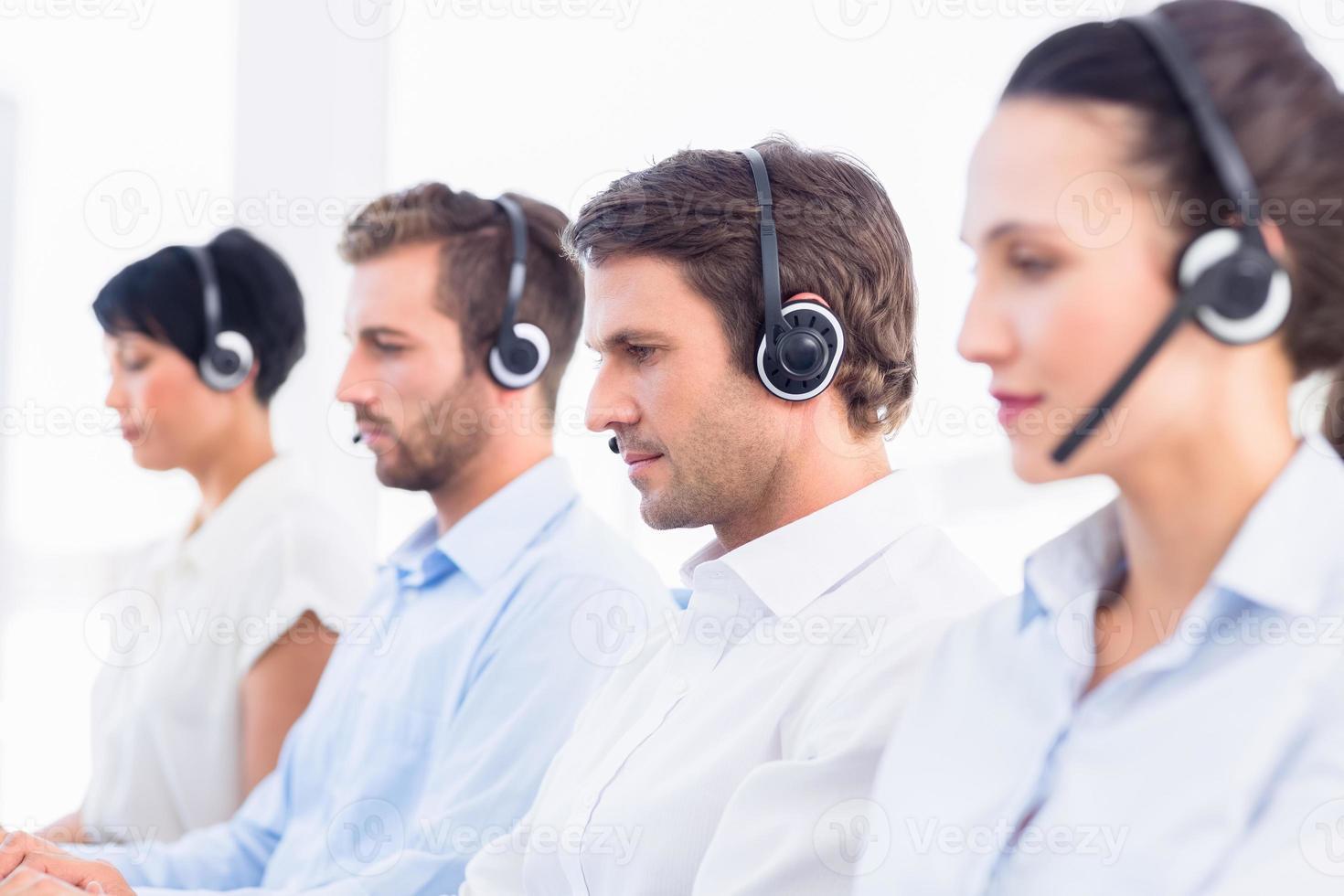 grupo de colegas de trabalho com fones de ouvido em uma linha foto