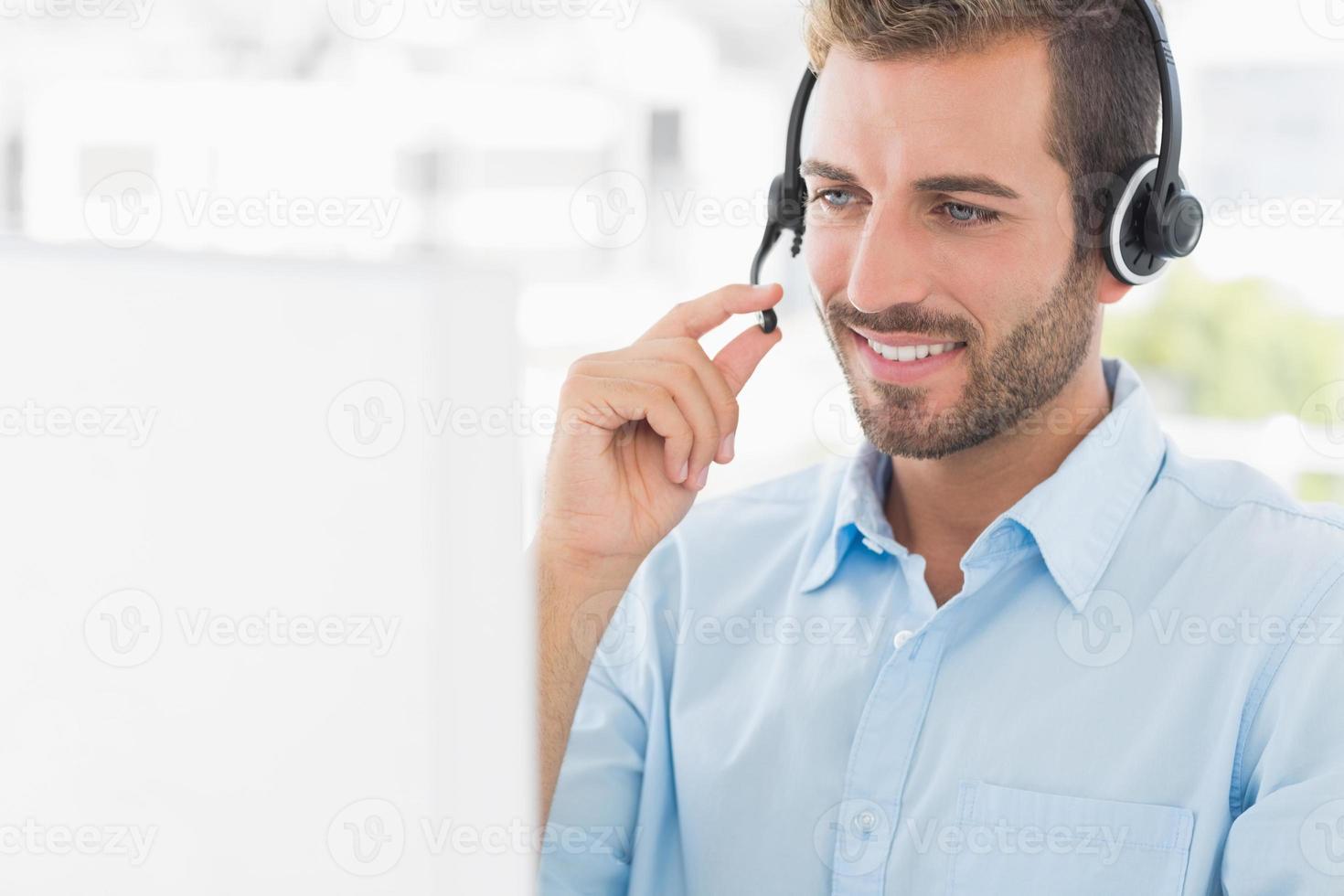 jovem casual com fone de ouvido usando o computador foto