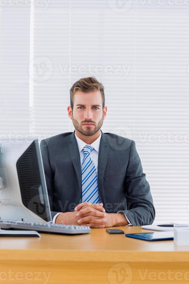 homem de negócios sério com o computador na mesa de escritório foto