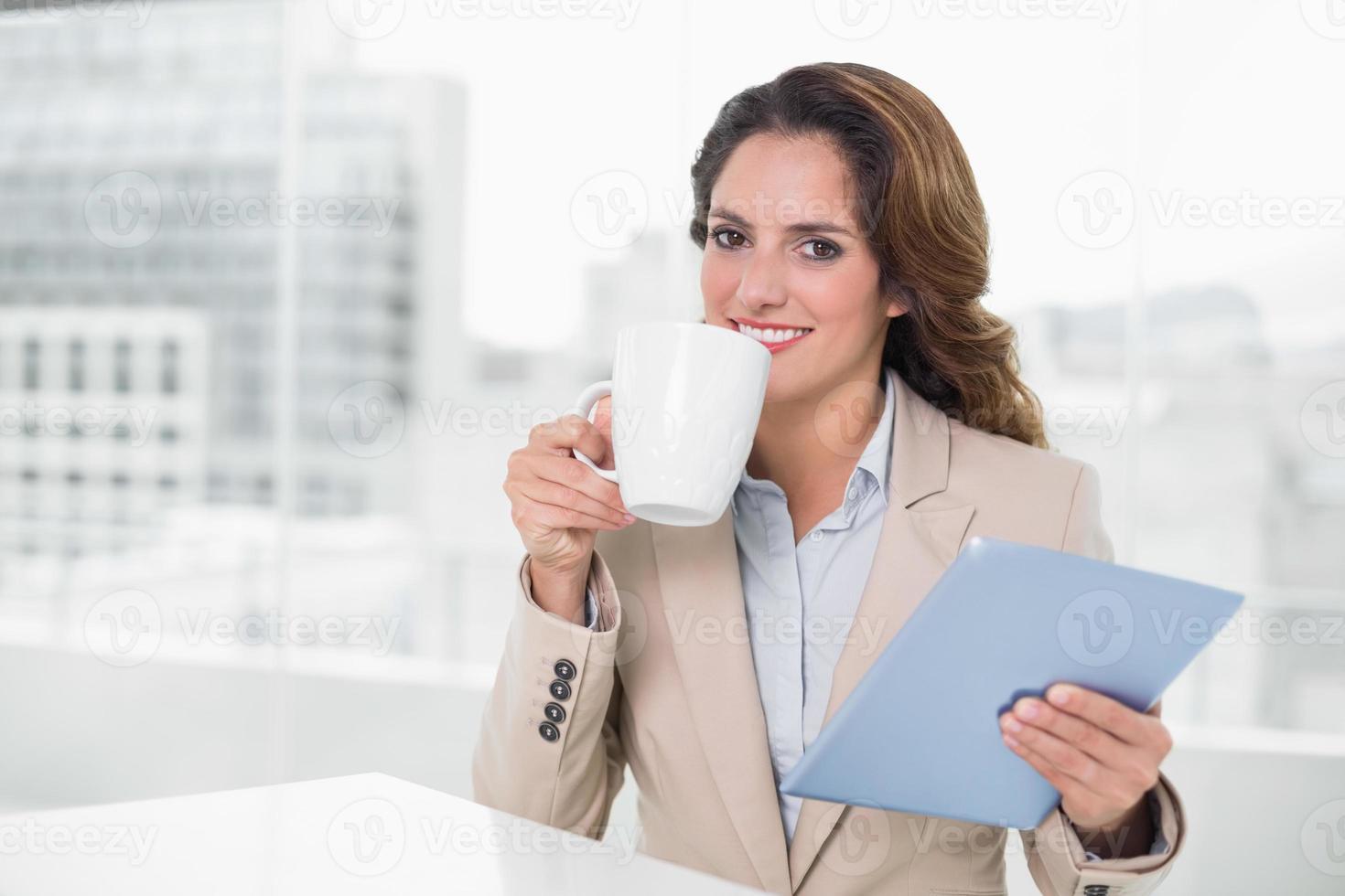 empresária de conteúdo bonita usando tablet bebendo café foto