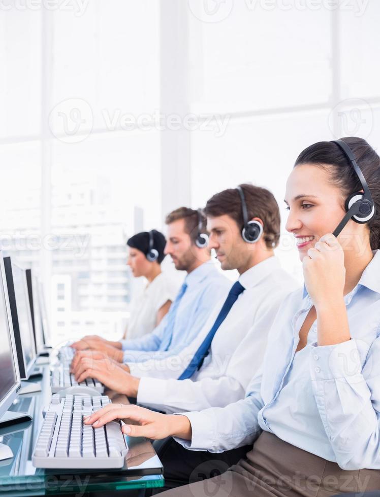 colegas de trabalho com fones de ouvido usando computadores foto