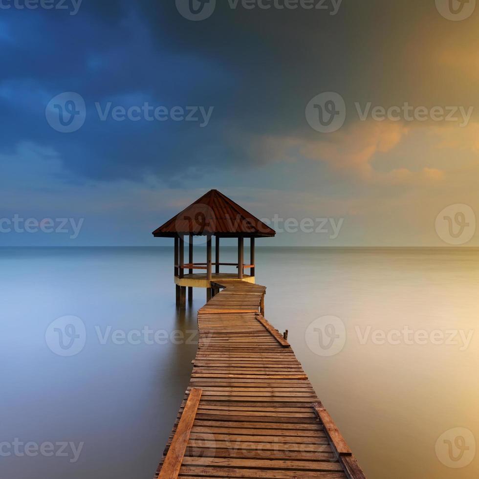 pôr do sol de pouso de madeira com pavilhão no mar foto