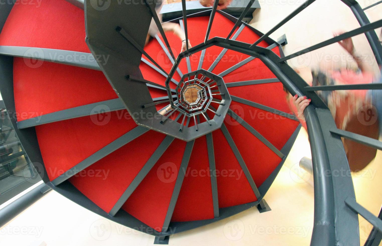 escada em espiral com tapete vermelho para uma subida vertiginosa foto