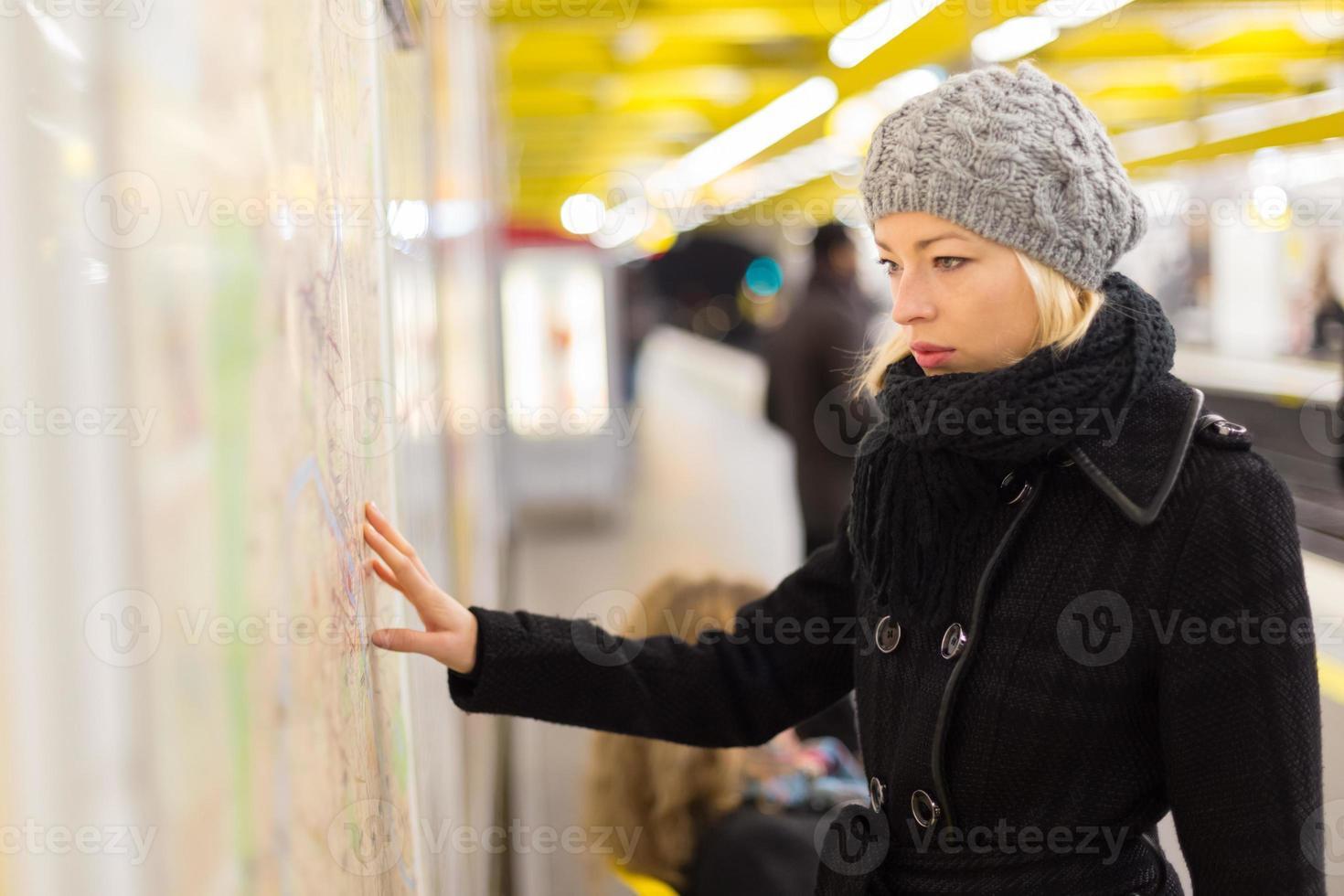 senhora olhando no painel de mapa de transportes públicos. foto