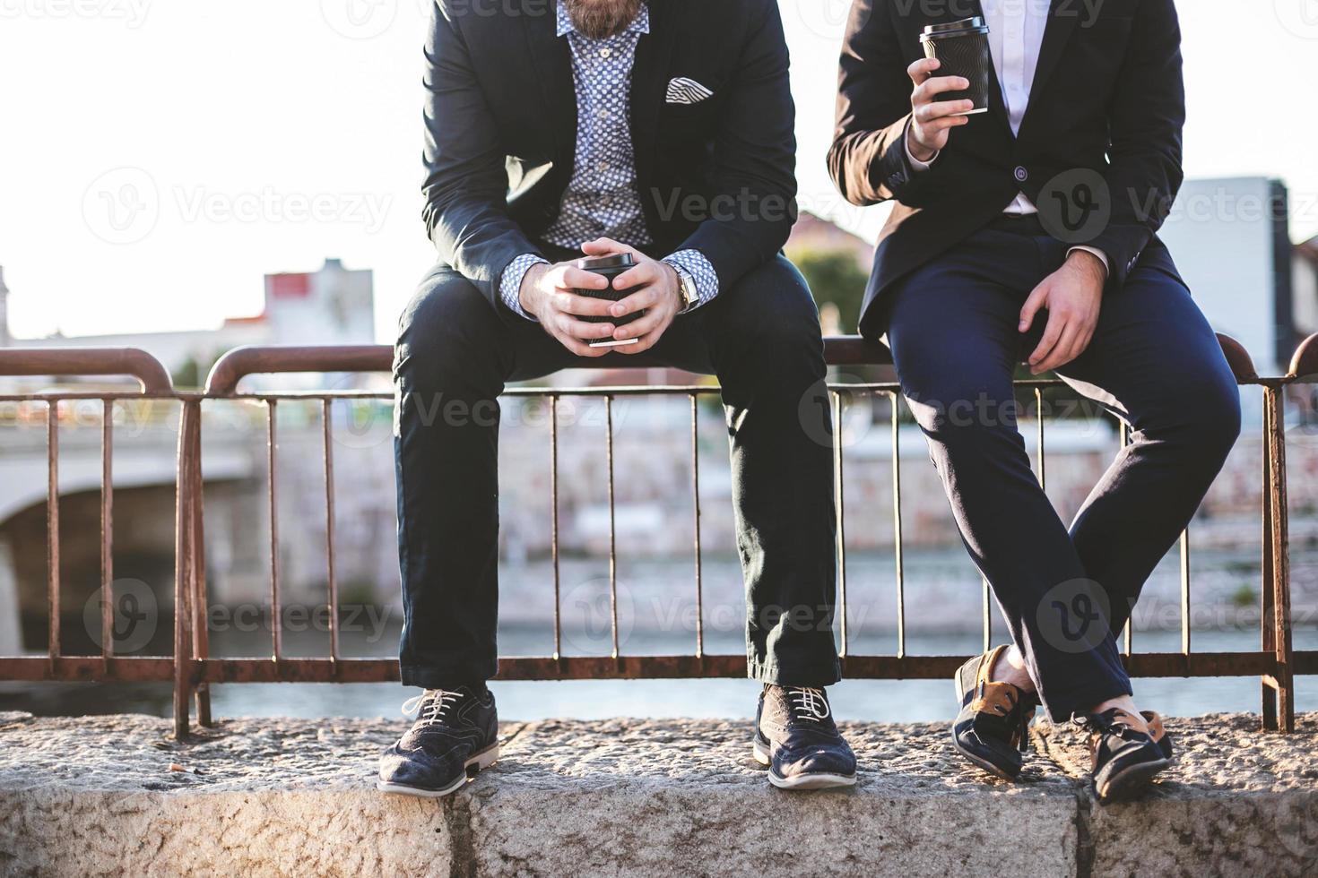 dois amigos hipster se divertindo lá fora, tomando café e conversando foto