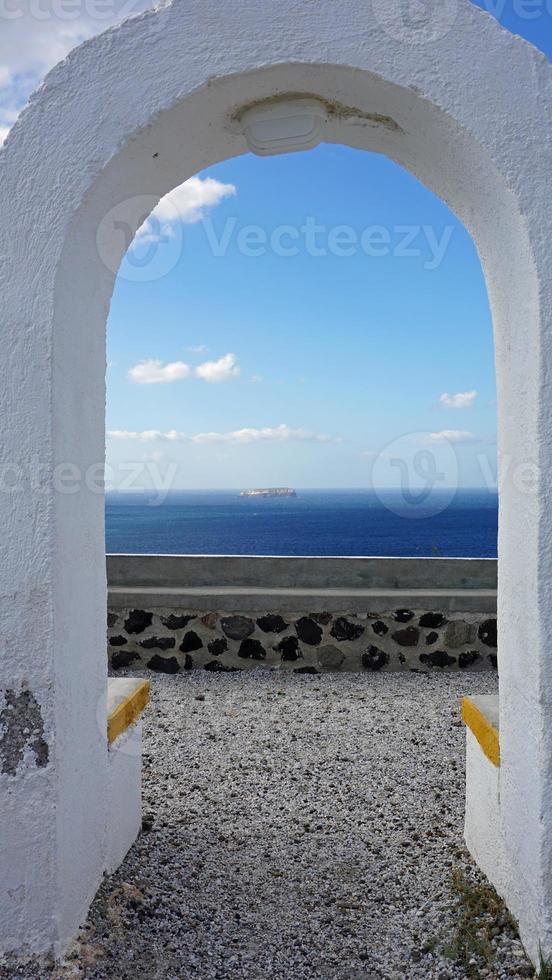 vista através do arco para o mar Egeu da ilha de santorini foto