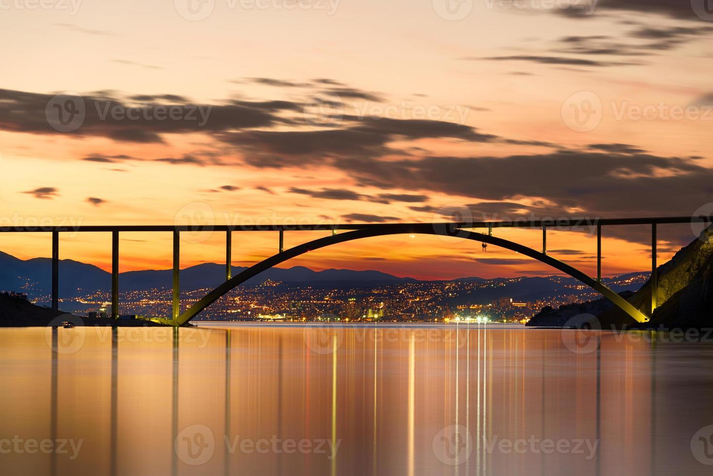 ponte para a ilha de krk ao pôr do sol, croácia foto