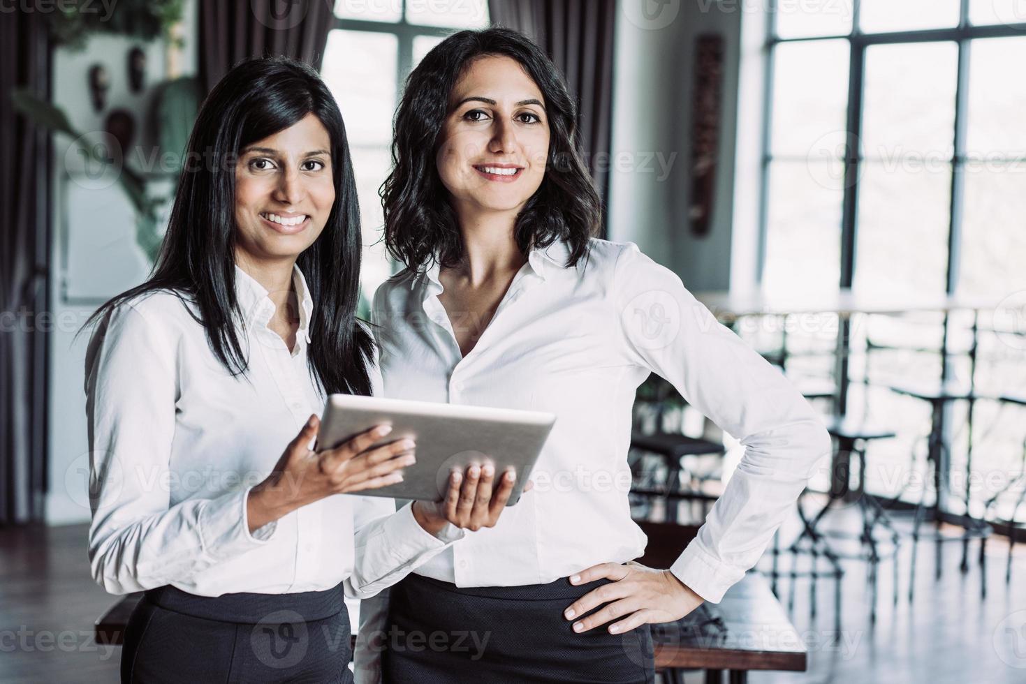 duas colegas alegres usando computador tablet no café foto