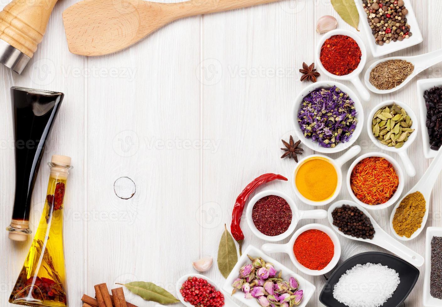 várias especiarias e condimentos em fundo branco de madeira foto