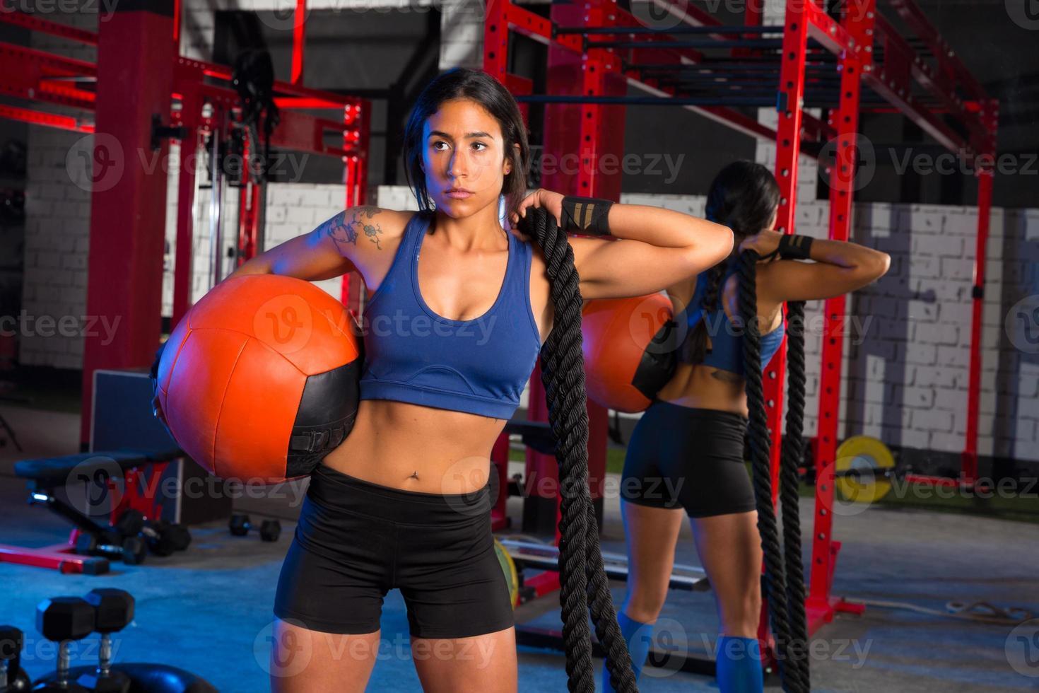 mulher de ginásio com bola e corda ponderada foto