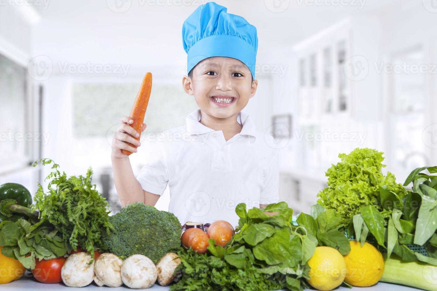 menino feliz chef com legumes frescos foto