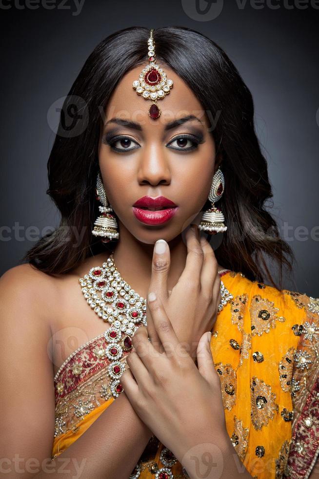 mulher indiana em roupas tradicionais com maquiagem de noiva e jóias foto