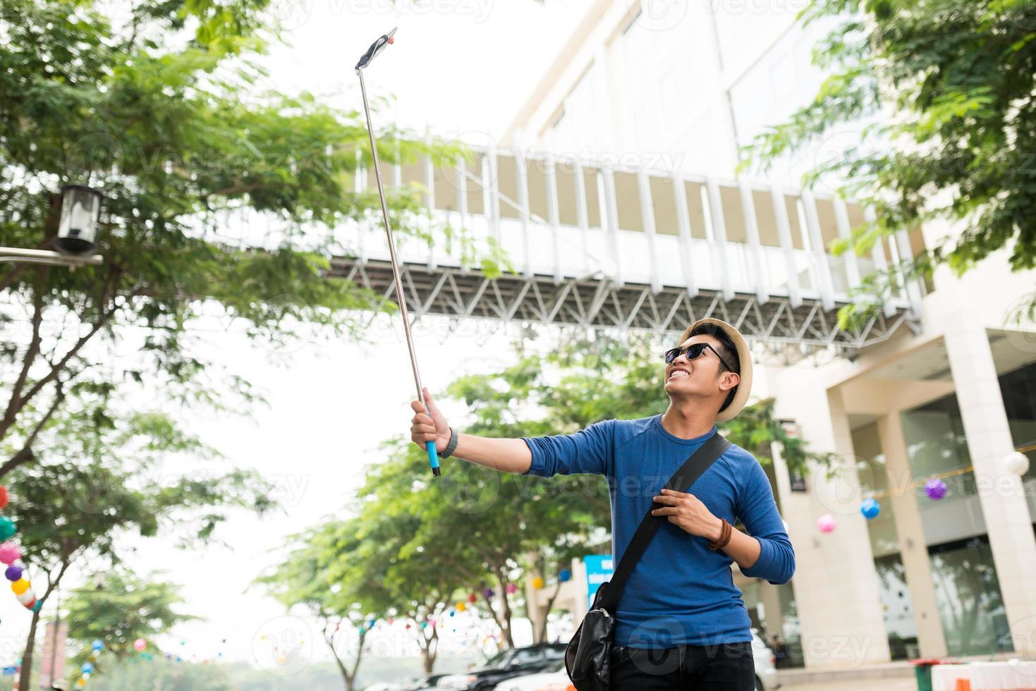 homem com vara de selfie foto