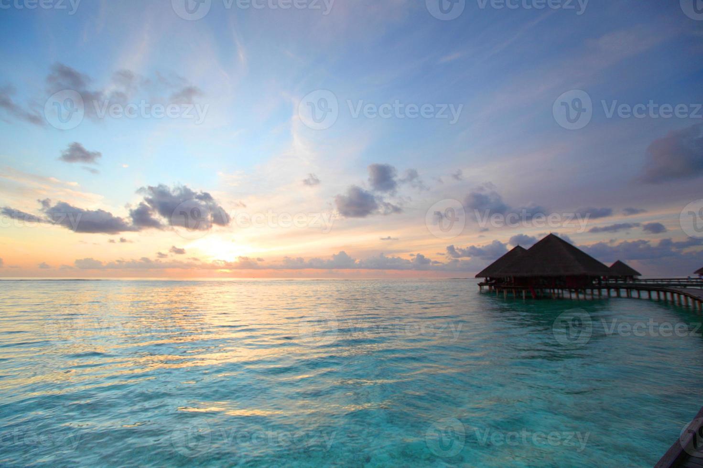casas maldivas no nascer do sol foto