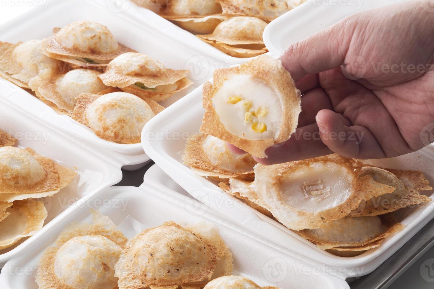 mão segurando o bolo de arroz de coco foto