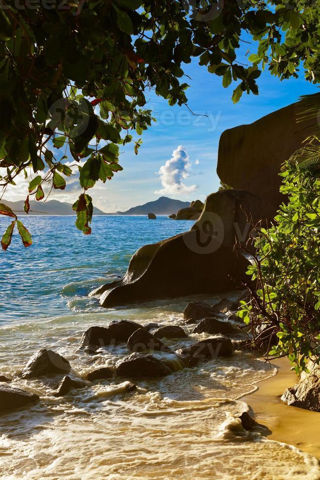 pôr do sol na praia fonte d'argent em seychelles foto