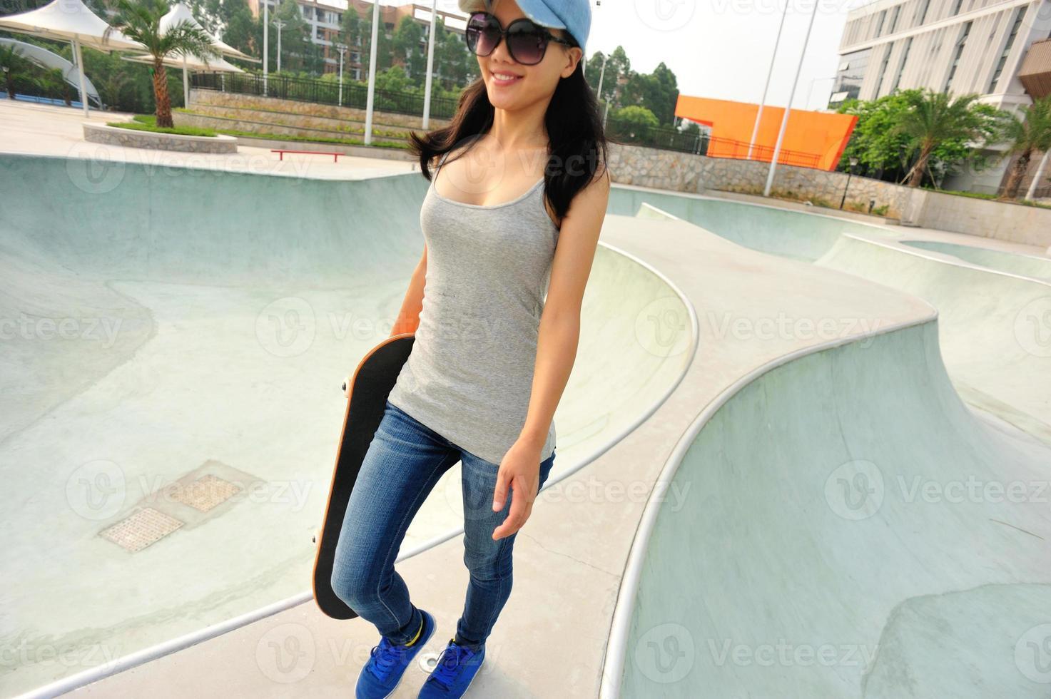 skatista mulher andando no skatepark foto