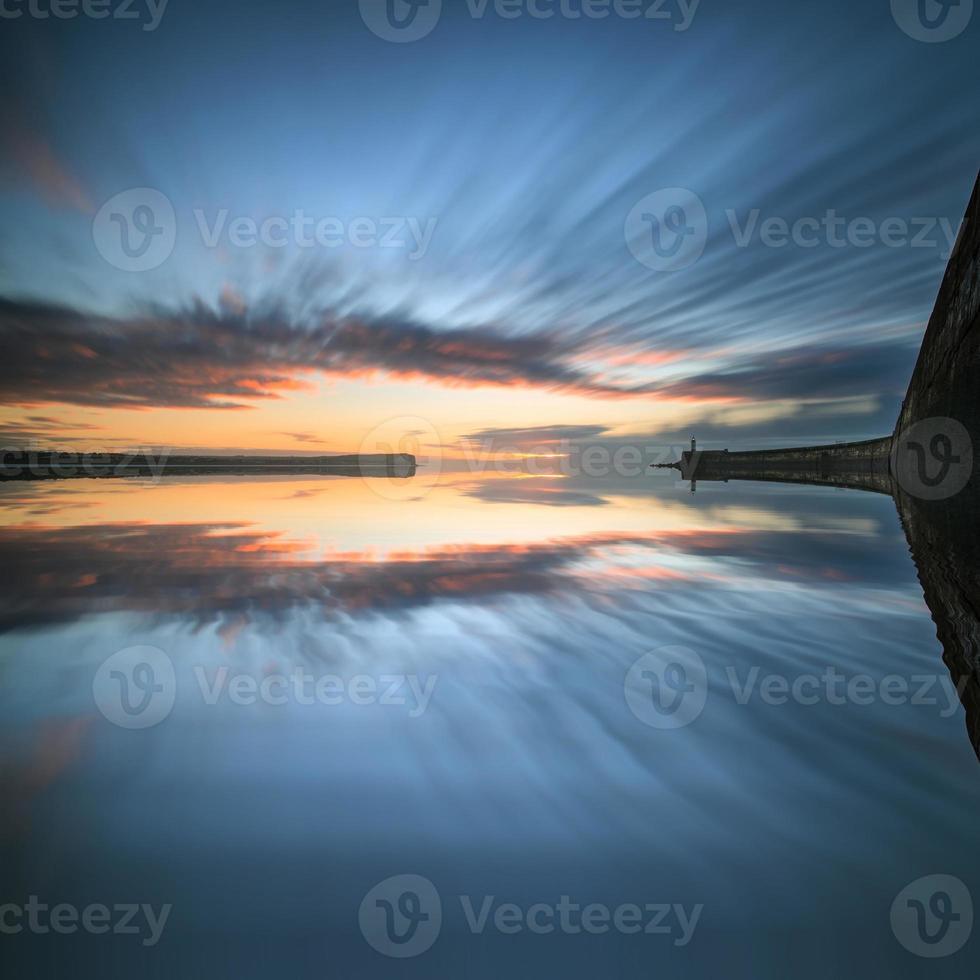 céu do nascer do sol sobre o oceano de águas calmas com farol e porto foto
