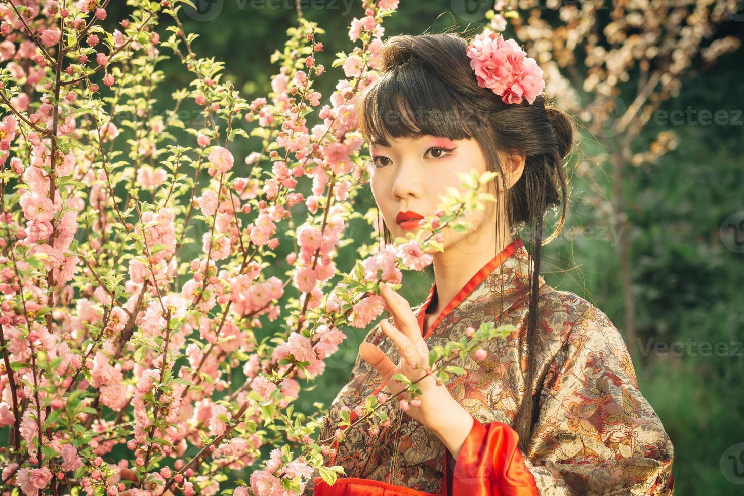 linda mulher asiática em flor de sakura foto