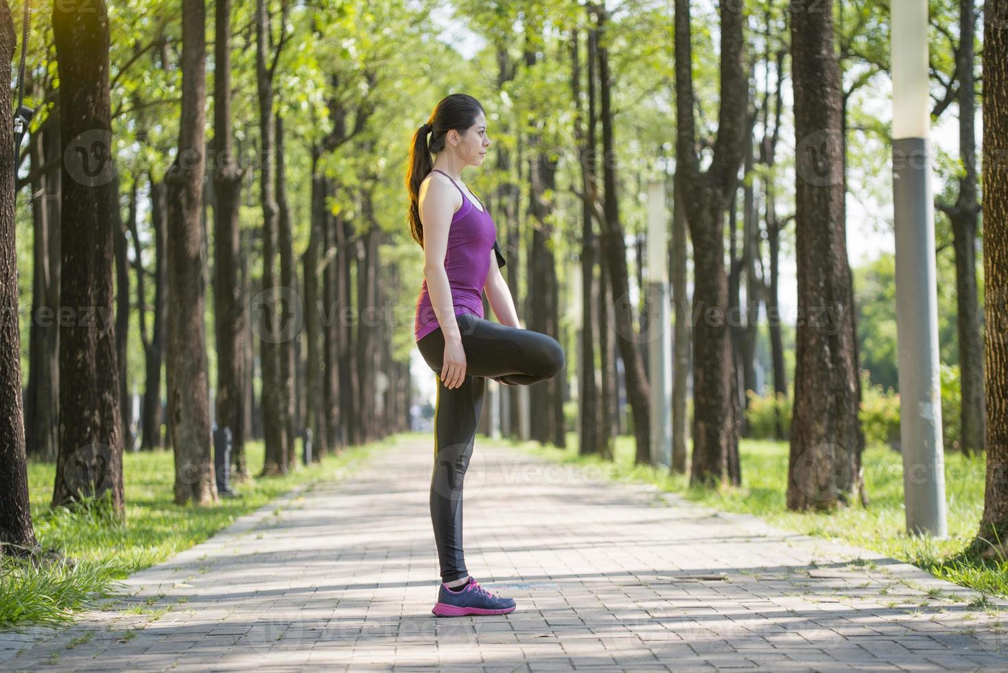 desportiva jovem asiática alongamento depois de correr na floresta foto