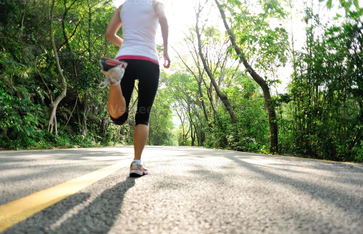 estilo de vida saudável fitness esportes pernas de mulher correndo na estrada da floresta foto