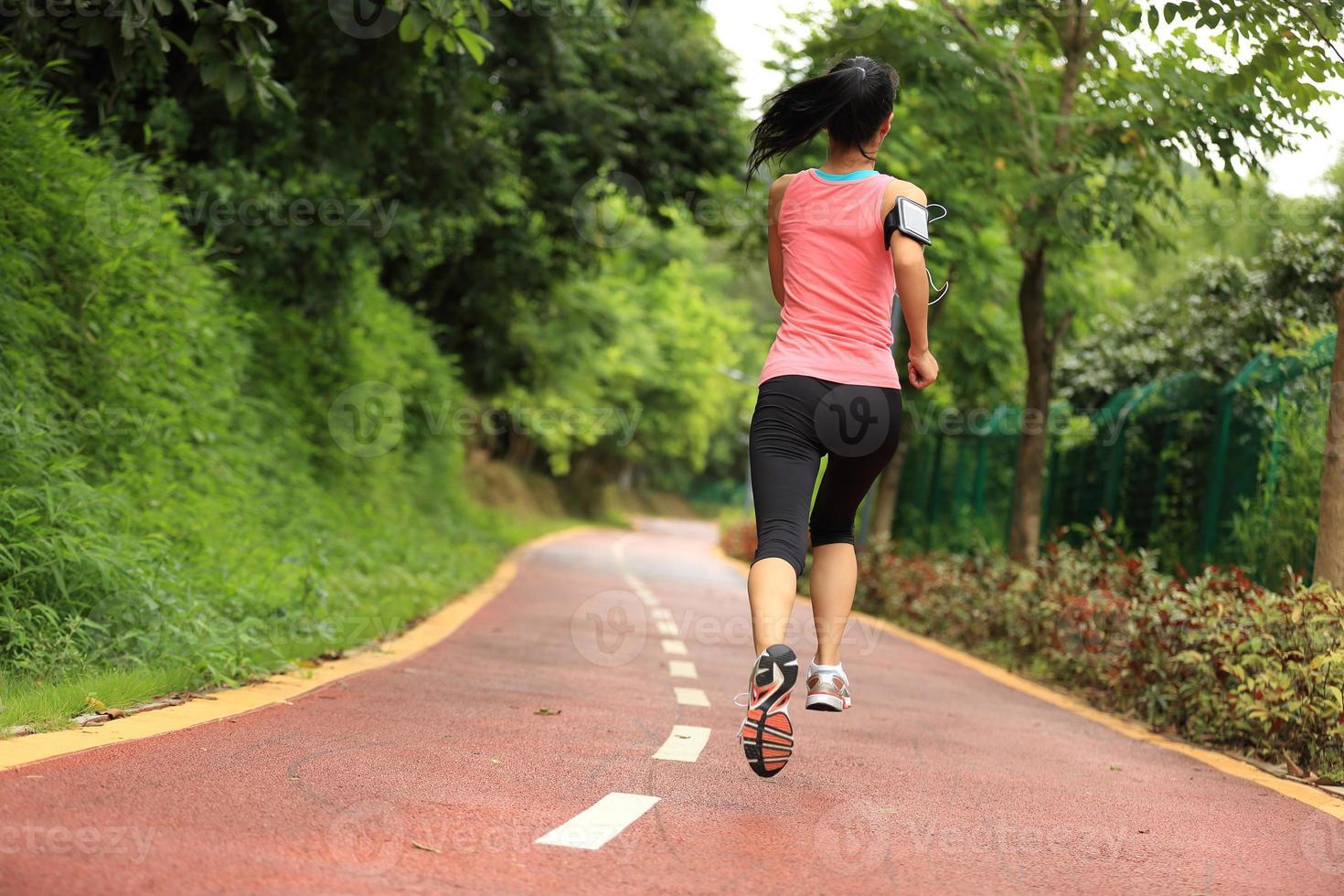 jovem mulher correndo por uma trilha do parque foto