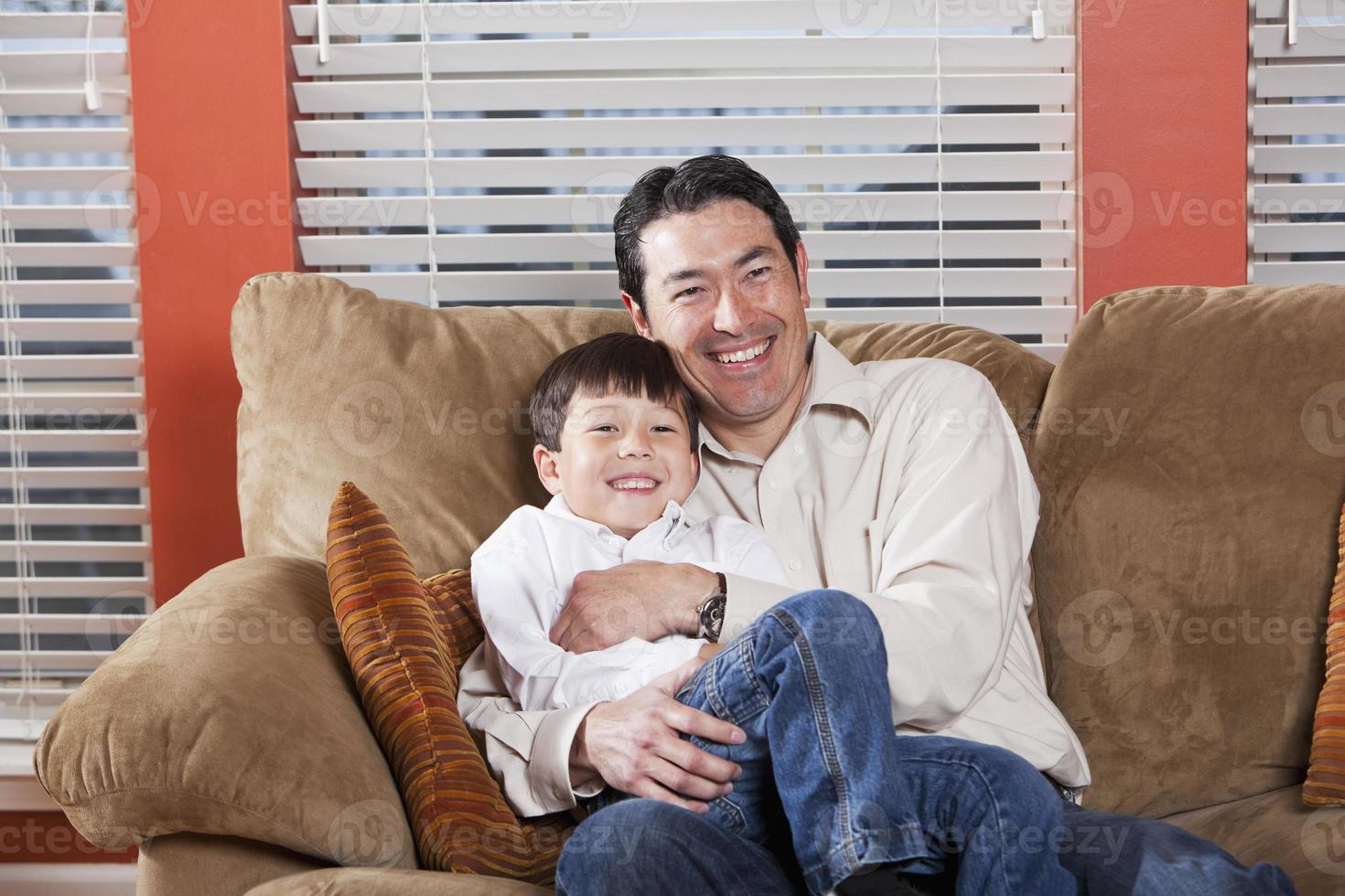 pai e filho sentado no sofá foto
