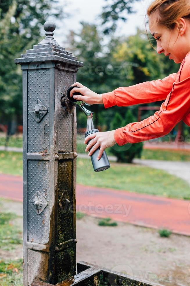 mulher derramando água em uma garrafa de esportes foto
