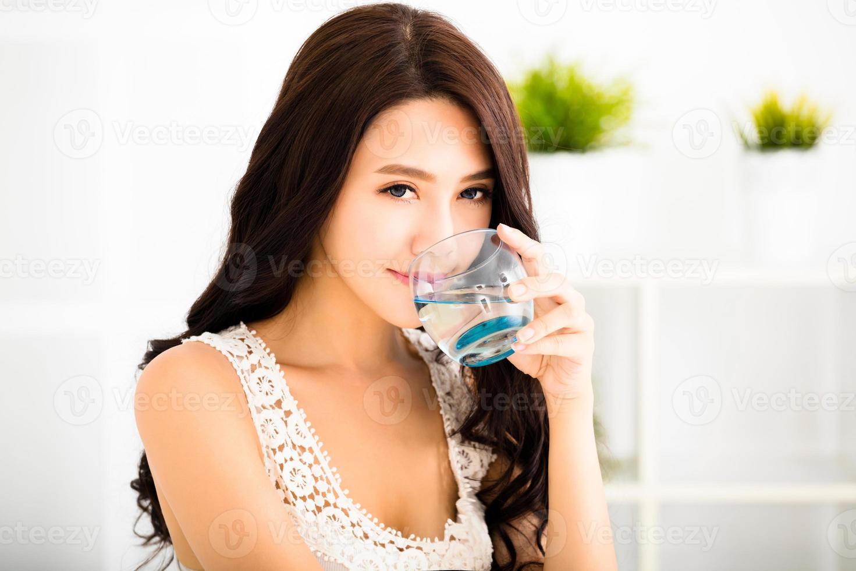 mulher sorridente jovem relaxada, bebendo água limpa foto