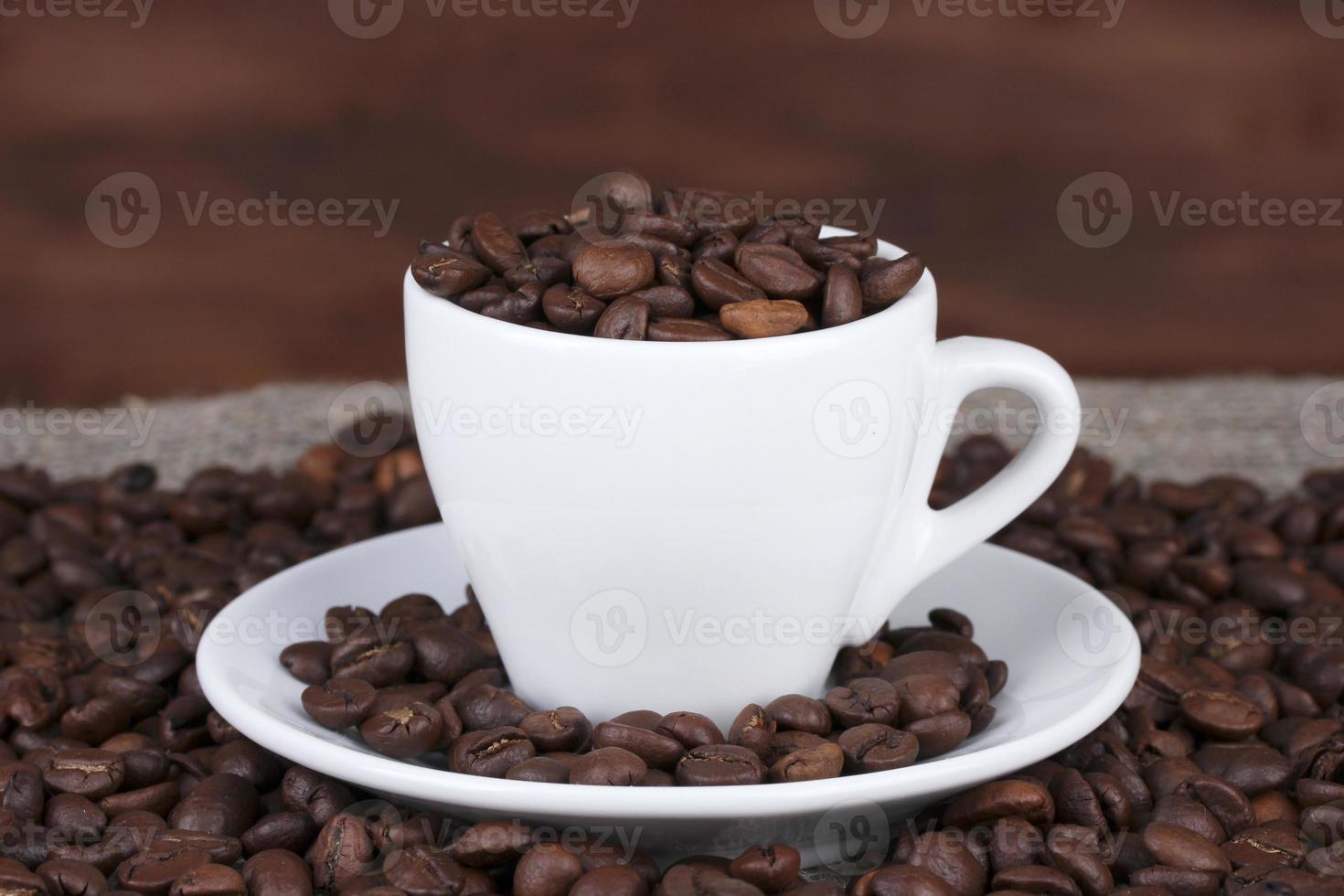 composição da xícara branca com close de grãos de café foto