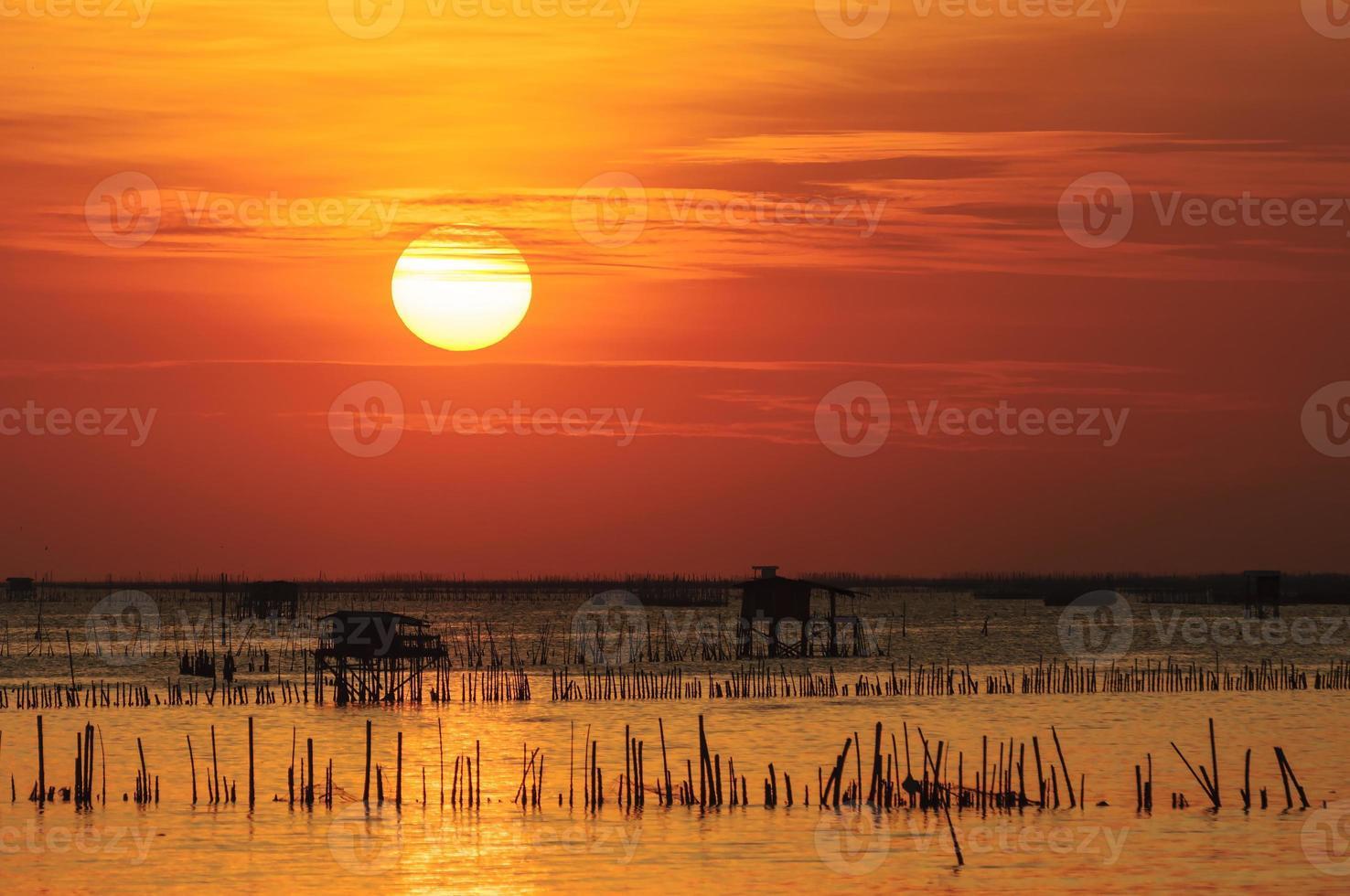 silhueta da casa de pesca tailandês ao pôr do sol foto