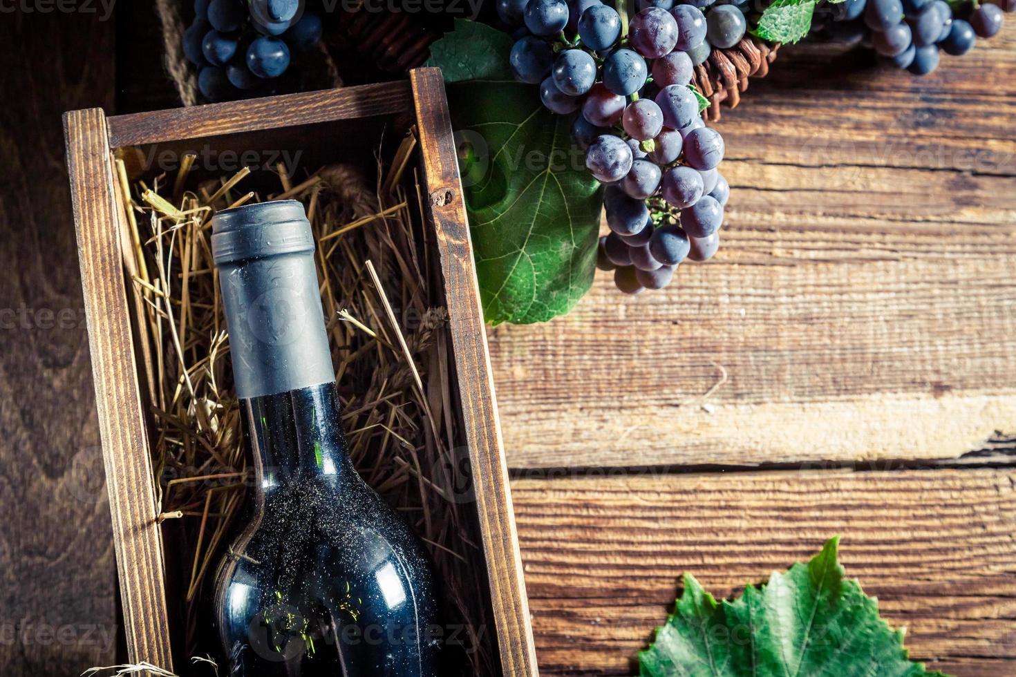 saboroso vinho tinto em caixa de madeira foto