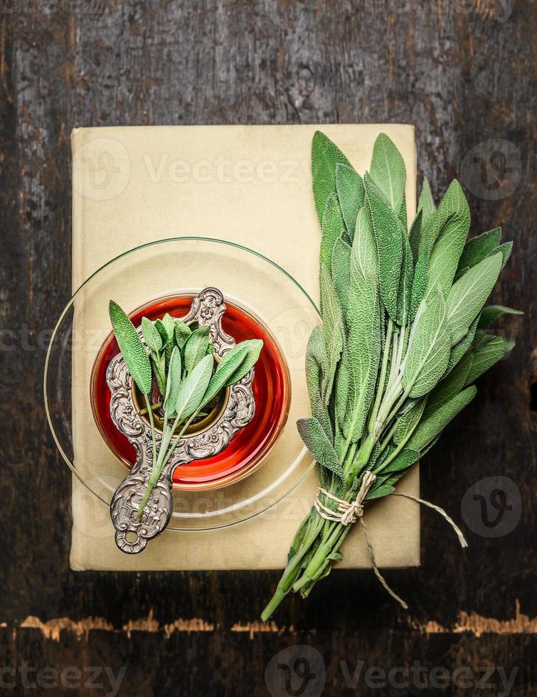xícara de chá de ervas sálvia com filtro velho, livros foto