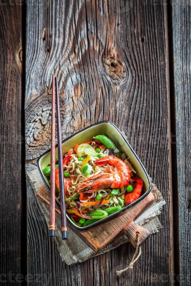 macarrão saboroso com legumes frescos e camarão foto