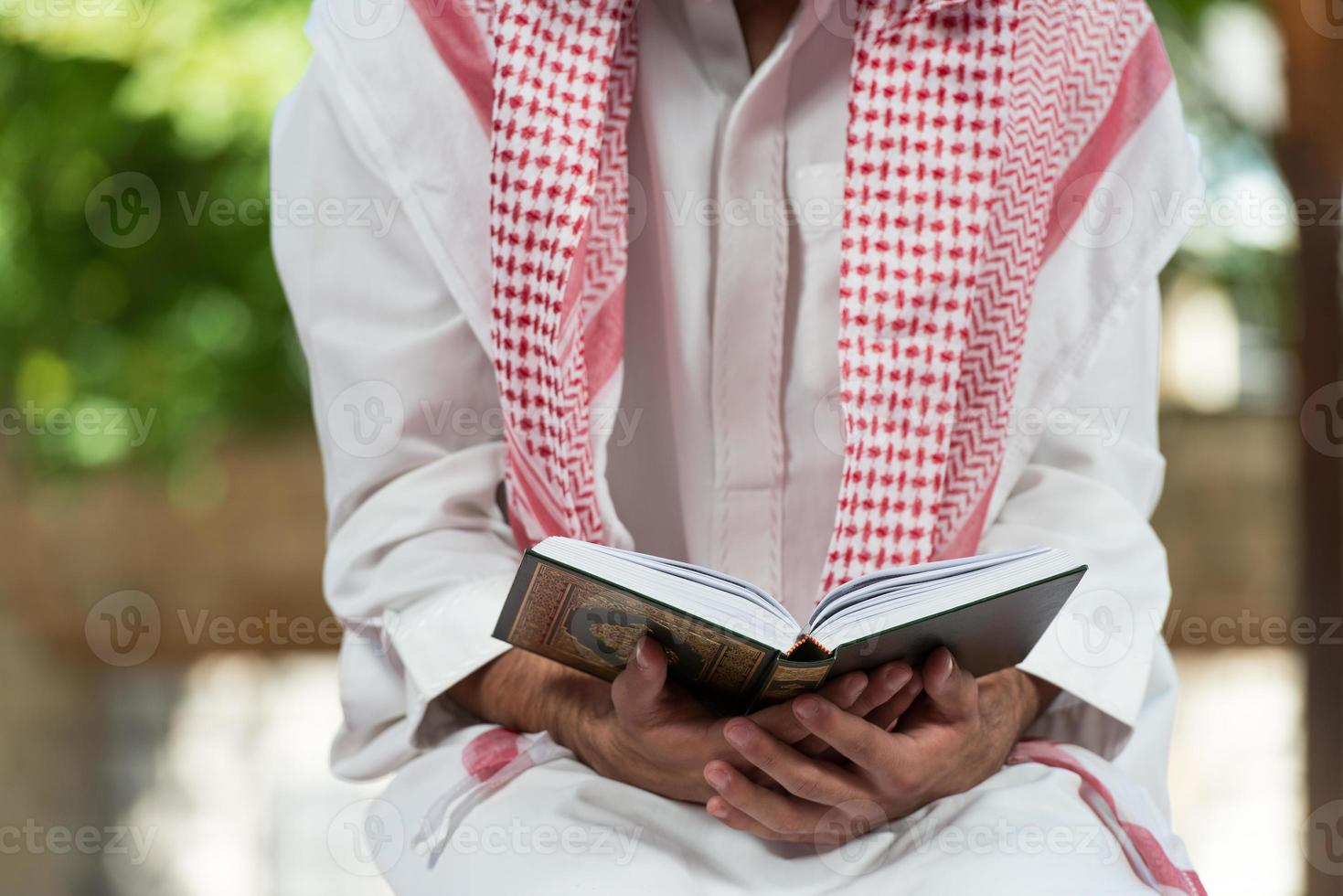 homem muçulmano em dishdasha está lendo o Alcorão foto