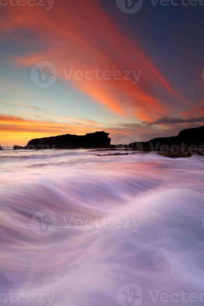 belo pôr do sol na praia de melasti em bali foto