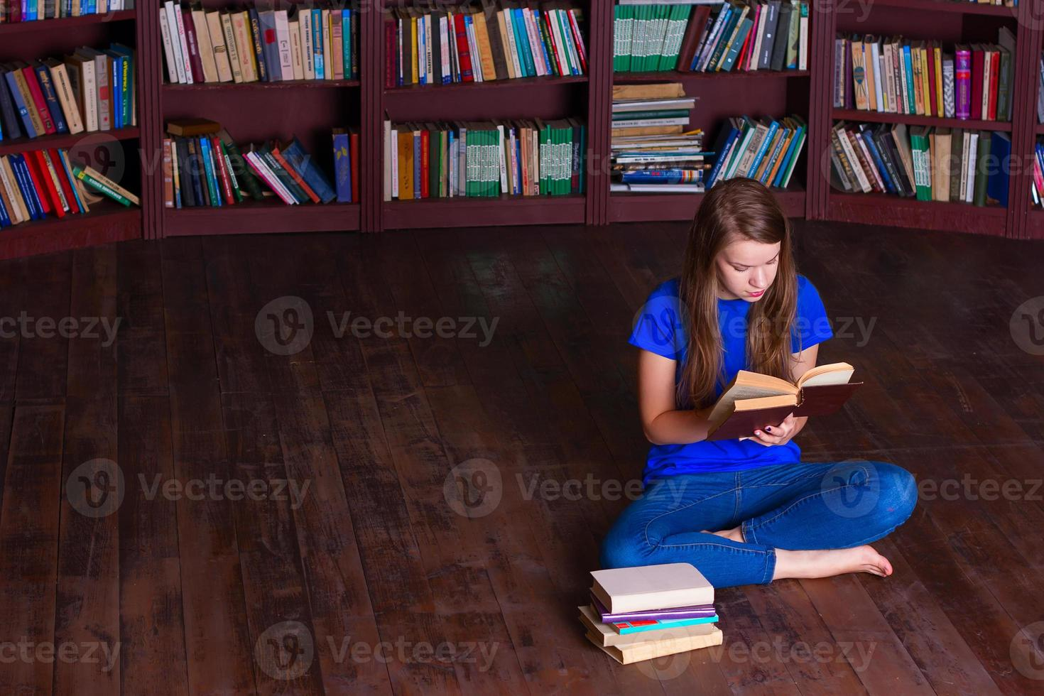 menina senta-se no chão na biblioteca foto