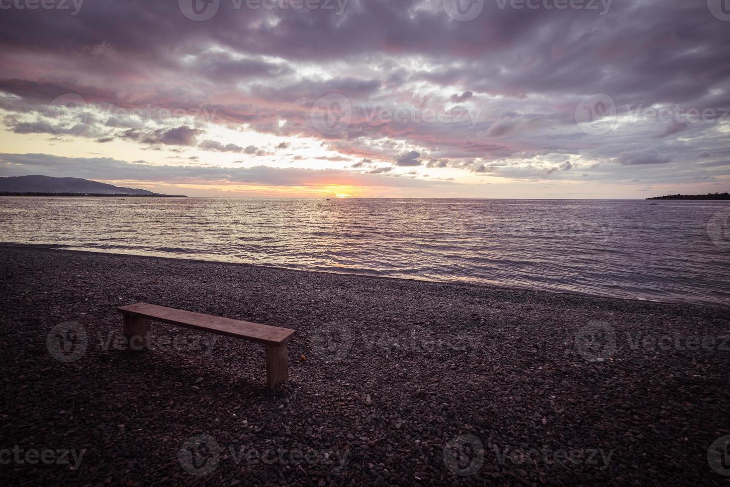 banco vazio na praia ao pôr do sol, marsala em tons foto
