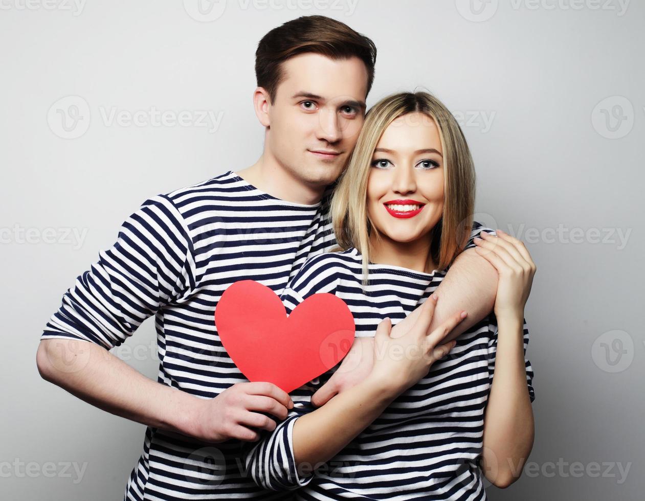 casal feliz no amor segurando coração vermelho foto