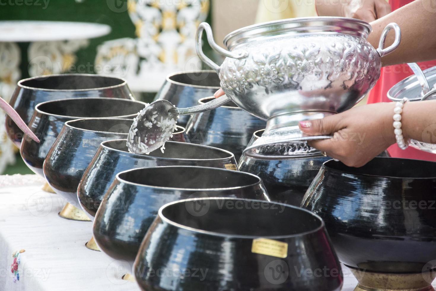 coloca ofertas de comida na tigela de esmolas de um monge budista foto