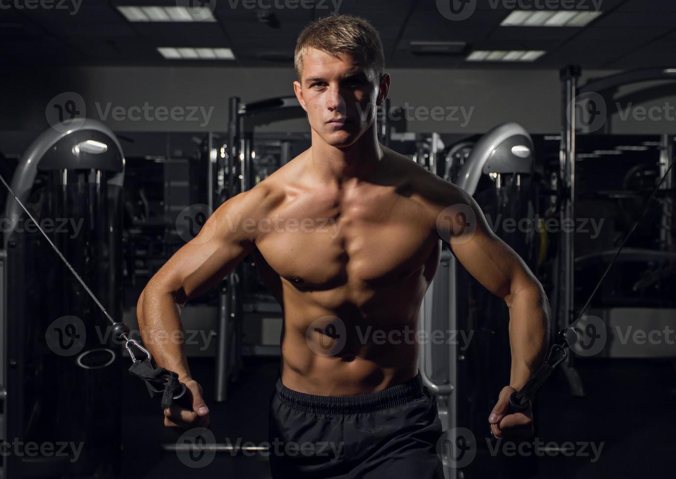 jovem Atlético, bombeando os músculos no cruzamento foto