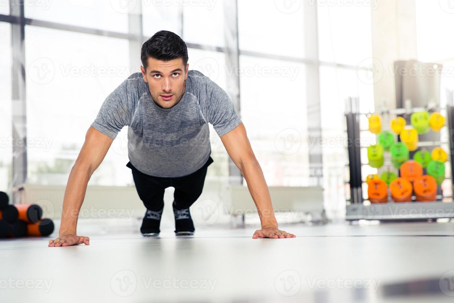 homem fazendo flexões no ginásio foto