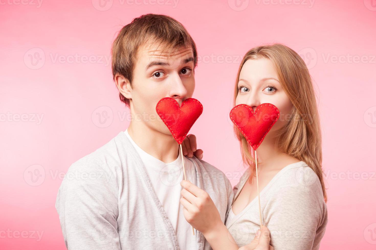 casal, escondendo os lábios atrás de pequenos corações vermelhos foto