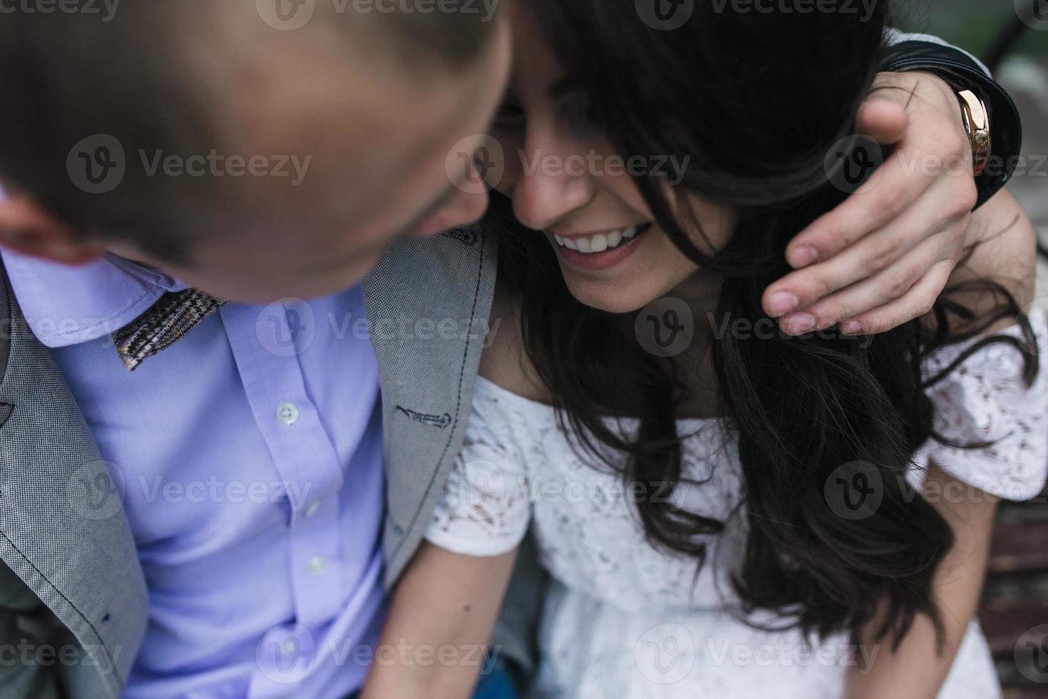 jovem casal europeu abraçando em um banco do parque foto