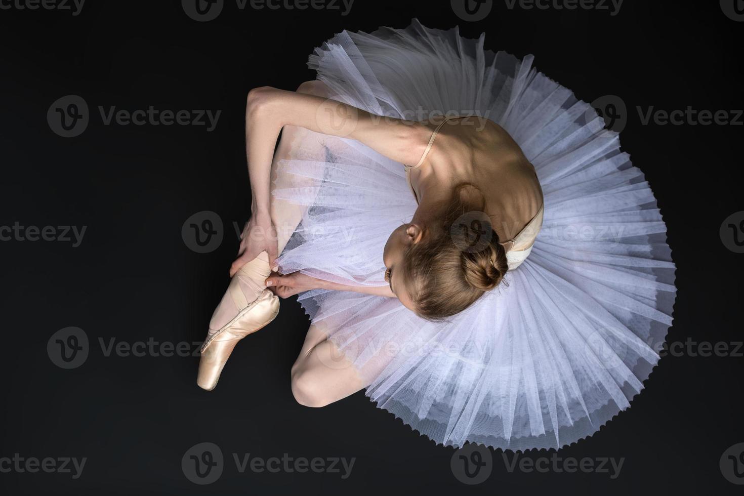 jovem bailarina amarrando ponta sentado no chão foto