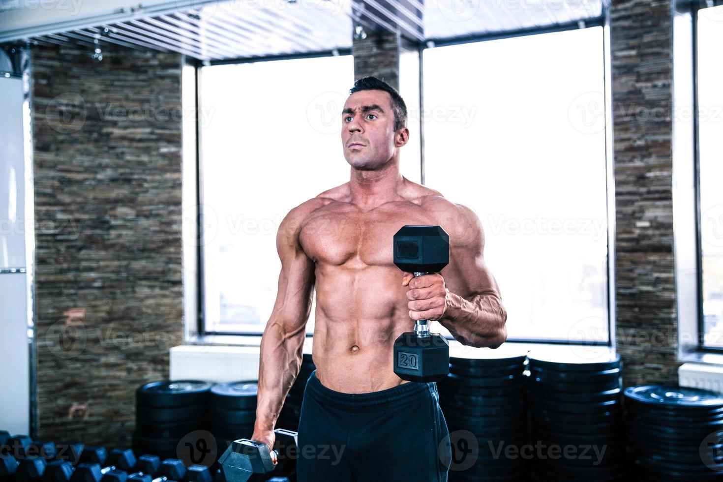 treino de homem musculoso com halteres foto