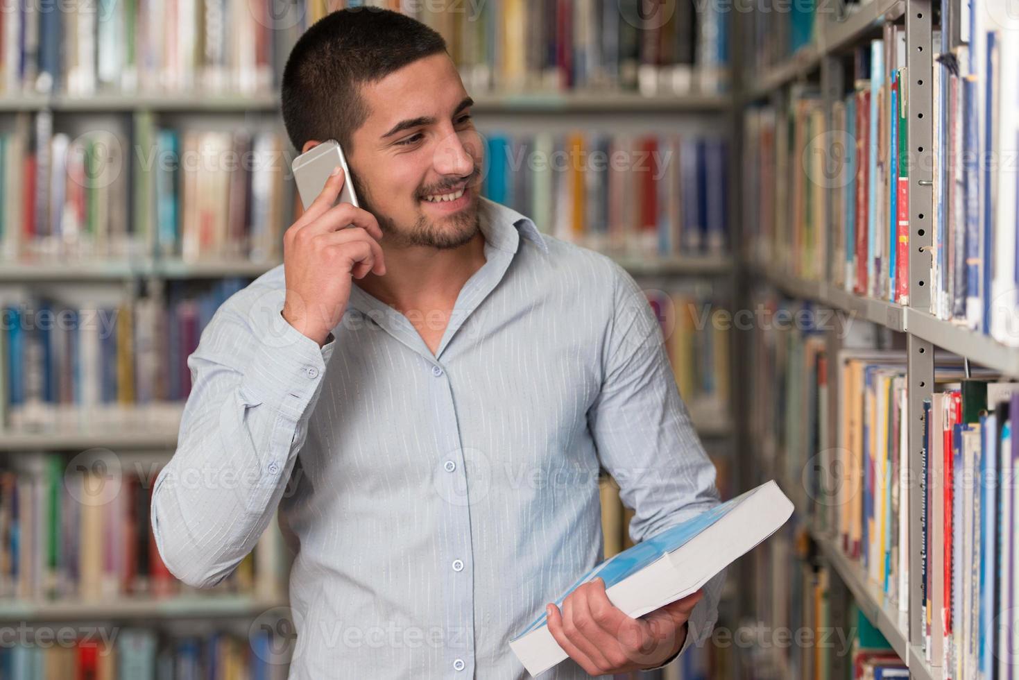 estudante do sexo masculino falando ao telefone na biblioteca foto
