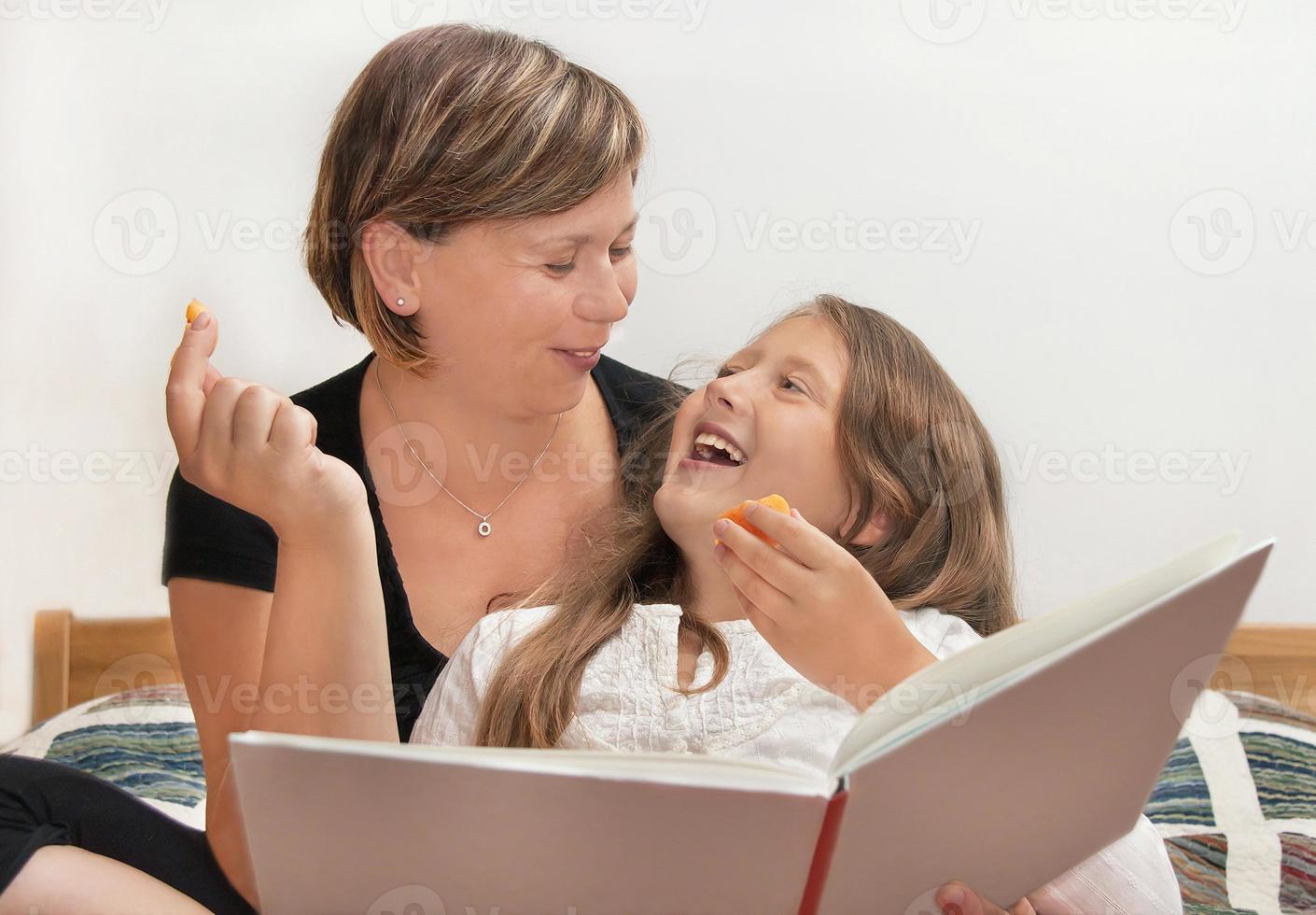 mãe e filha com livro foto