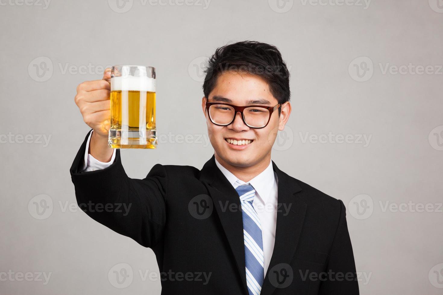 aplausos de empresário asiático com caneca de cerveja foto