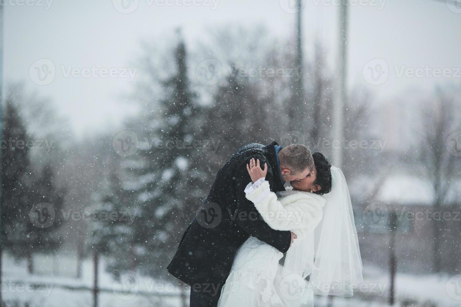noiva e noivo andando na neve foto